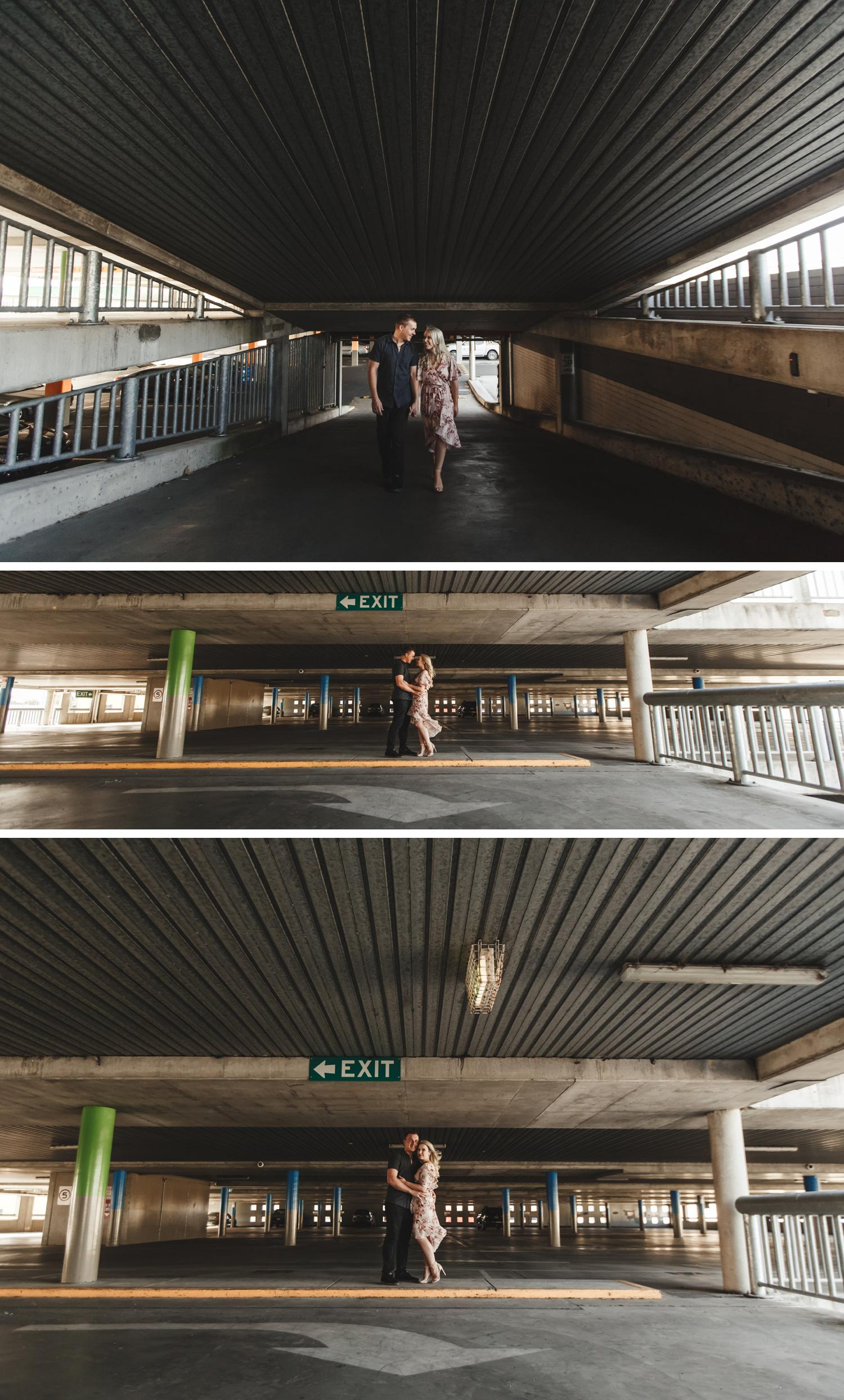 Couple Embracing Car Park Engagement Shoot, Wide Angle Shot of Bride and Groom Embracing by Danae Studios